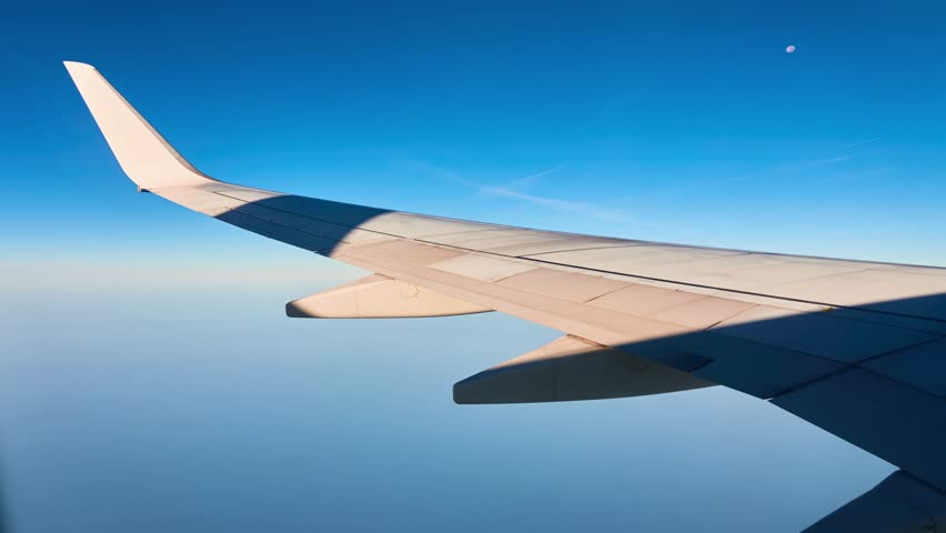 Wing of flying plane against background of sky horizon. View from porthole. | Shutterstock HD Video #1011494192