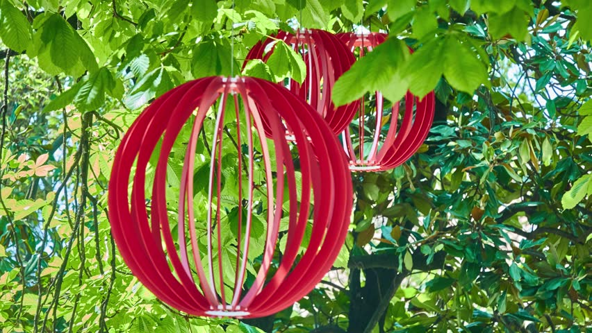 Red wooden balls hang in foliage on tree in summer city park. | Shutterstock HD Video #1011494222
