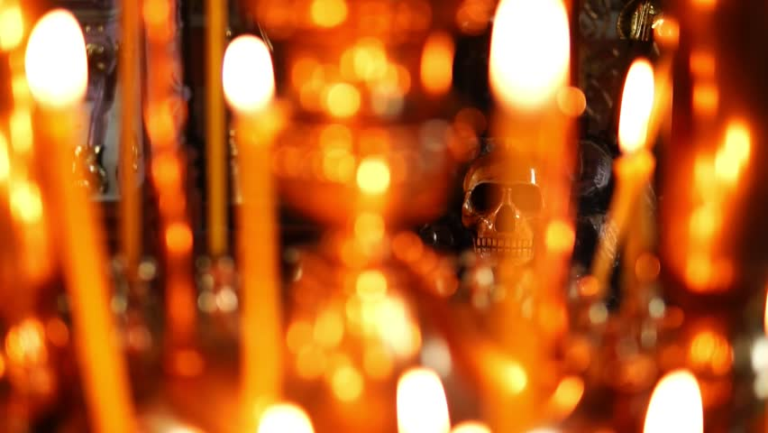 Skull in focus, in the foreground burning candles in the Christian Orthodox Church | Shutterstock HD Video #1011508682