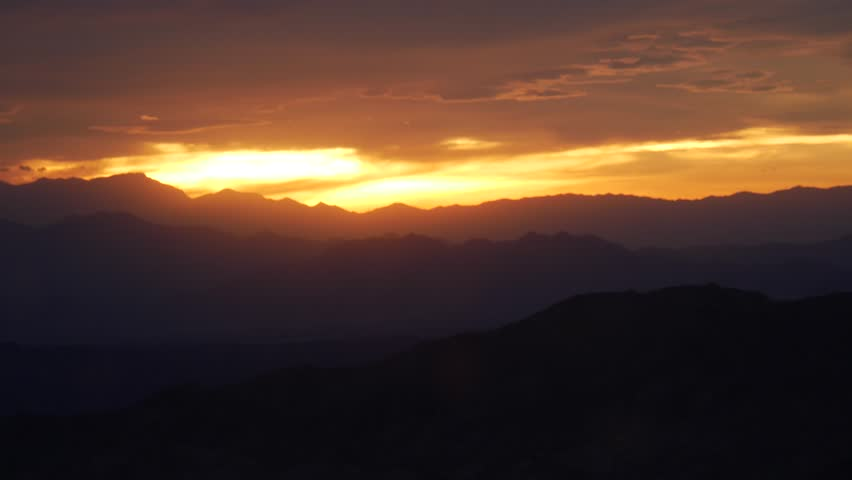 Spectacular fiery orange sunset over Grand Canyon with silhouetted mountains and a cloudy sky seen from the Southern Rim