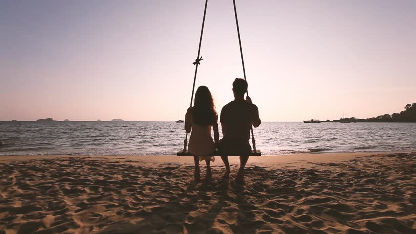 Romantic getaway, couple in love sitting together on rope swing at sunset beach, silhouettes of young man and woman on holidays or honeymoon | Shutterstock HD Video #1011528662