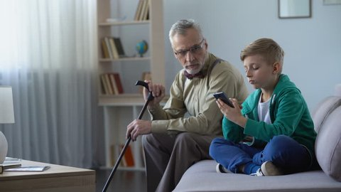 Boy scrolling blog pages in smartphone, his grandfather feels abandoned, upset