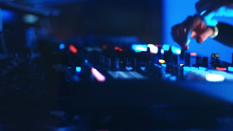 A DJ behind the console, on stage, mixing tracks in atmospheric dance party strobing and flashing lights.