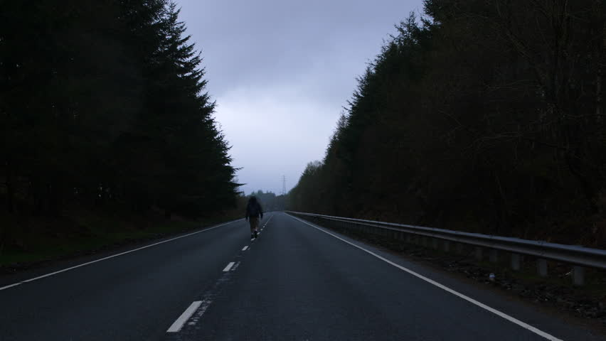 Young man walking down empty road and hitch hiking in Scottish Highlands UK. Hiker exploring long empty road whilst travelling in Scotland UK