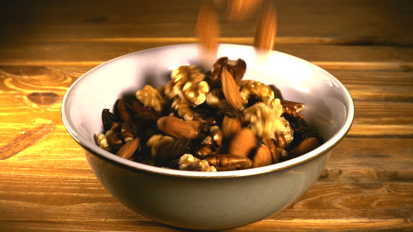Slow motion shot of a healthy snack of mixed nuts and raisins, pouring into a ceramic bowl on a pine worktop.