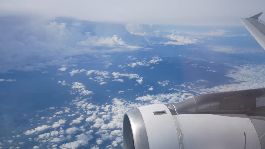 View of the sky above cloud level from the cabin window of airplane (plane) flying in the sky in clear day with some cloud (See plane engine and wing)-4K UHD video movie footage short #1011654842