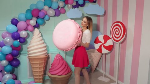Happy girl in bright clothes holding in his hand a huge marshmallow in the Studio with huge plastic candy. Sweet food and happiness concept. Barbie style. Candy girl.
