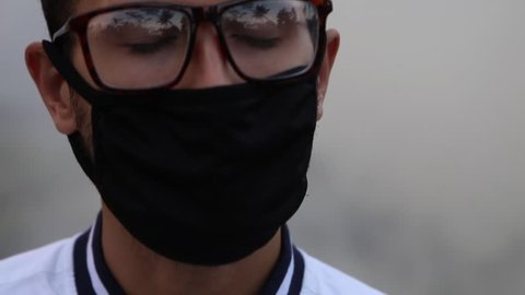 Man covered his face with anti-pollution mask closing eyes