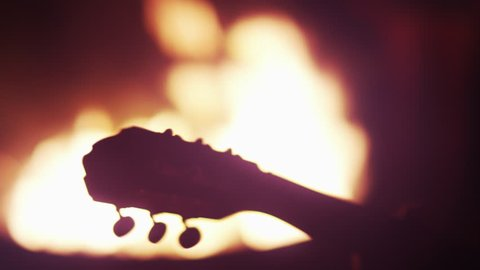 Guitar Neck Silhouetted At Bonfire
