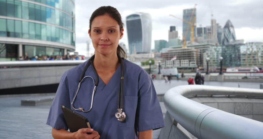 Happy millennial woman nurse or doctor smiling at camera outside hospital facility. Female Medical professional holding tablet computer and looking at lens. 4k | Shutterstock HD Video #1011683822