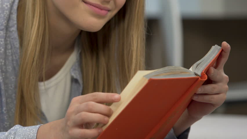 Girl reading book for self-education, preparation for literature examination