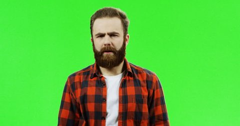 Portrait of the good looking Caucasian man with a beard standing in front of the camera and doing knock knock gesture, then waving his hand on the green screen background. Chroma key.