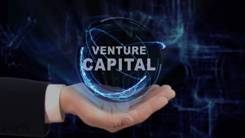 Painted hand shows concept hologram Venture Capital on his hand. Drawn man in business suit with future technology screen and modern cosmic background | Shutterstock HD Video #1011690422