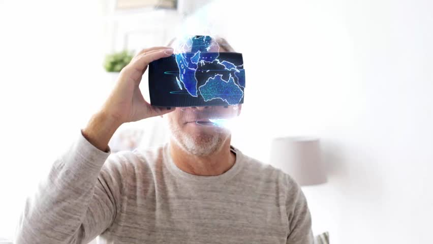 technology, augmented reality and people concept - senior man in vr headset or 3d glasses with virtual earth projection at home