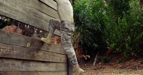 Side view of Caucasian military soldier climbing a wooden wall at boot camp during obstacle course