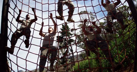 Military troops climbing a net during obstacle course at boot camp