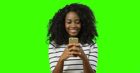 Pretty cheerful african american young woman with curly hair chatting with somebody on the smartphone while typing and smiling on the green screen background. Chroma key.
