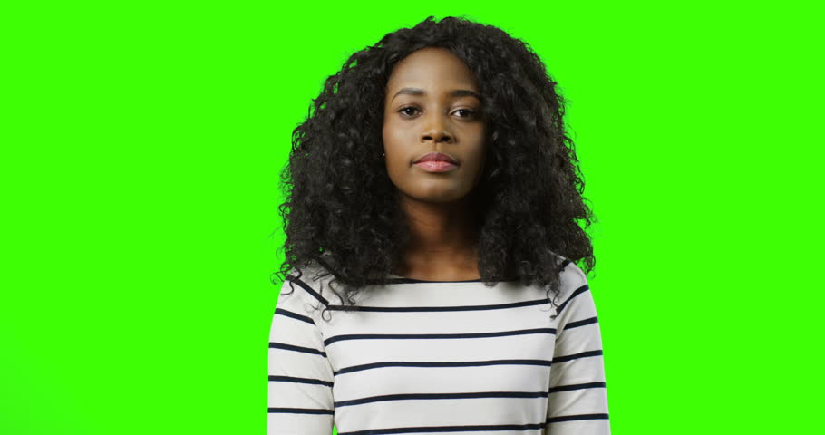 Close up of the young African American pretty woman standing on the green screen background and doing hush hush or be silence gesture with a finger near lips. Chroma key. | Shutterstock HD Video #1011706592