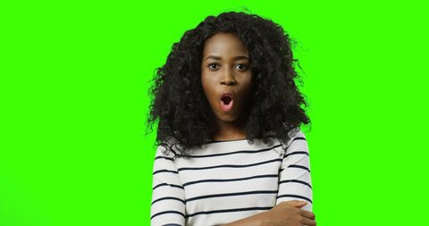 Young beautiful curly African american woman in the striped blouse making wow face and pointing up with her finger. Green screen. Chroma key.