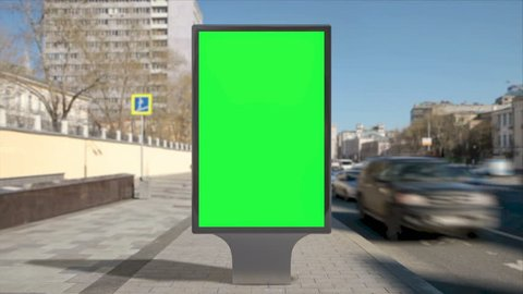 Street billboard stand with green screen on pavement and time lapse city background. Seamless loop.