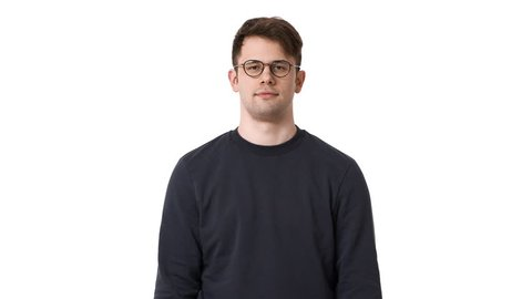 Portrait of happy man 20s wearing black sweatshirt and glasses smiling and winking, isolated over white background. Concept of emotions