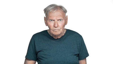 Portrait of angry old aged man 80s in basic t-shirt posing with strict gaze and asking keep silence putting index finger on lips slow motion, isolated over white background