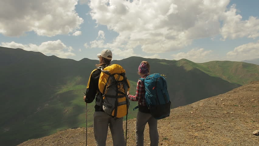 Wanderlust: hikers hiking with heavy backpacks in mountains.People hiking climbing mountains enjoy summer vacation travel adventure. Couple travel in summer hiking mountains. People in nature concept | Shutterstock HD Video #1011758852
