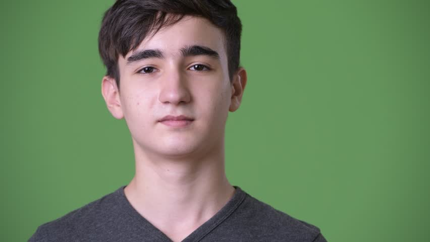 Young handsome Iranian teenage boy against green background | Shutterstock HD Video #1011761432