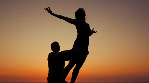 Silhouette of young woman and man doing pair yoga on sea beach at sunset. Meditation. Couple practicing acro yoga. Flexibility workout at nature background. Slow motion