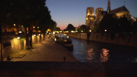 Lovely view of Notre Dame Cathedral across the River Seine in Paris. Night scene of historic French landmark near body of water in France