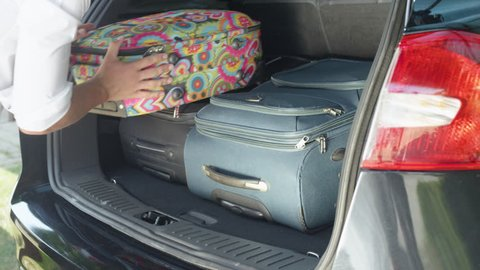 CLOSE UP: Unrecognizable young traveler packing baggage in the spacious boot of his large black car parked in the sunny suburban driveway. Unknown man in white shirt putting travel bags in his SUV.