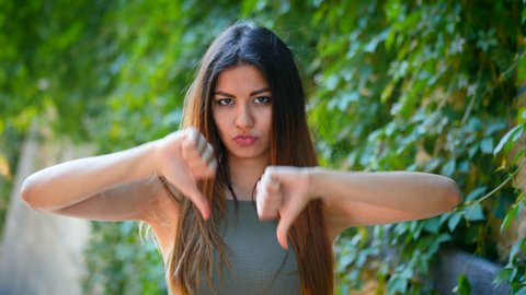 Young beautiful woman standing on green foliage background expressing discontent and showing thumb down gesture at camera. Portrait of girl with sign of dislike