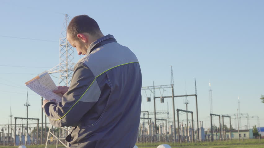 angry Worker at Electrical Substation. Worker with blueprints and clipboard in meeting at electrical substation. angry and nervous. Problem in work