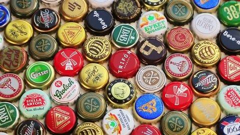 Moscow, Russia-30, 2018: beer bottle caps background, mix of different world brands: grolsch, Bud, Bavaria, Miller, Heineken, Baltika; Corona Extra, etc. Rotation video