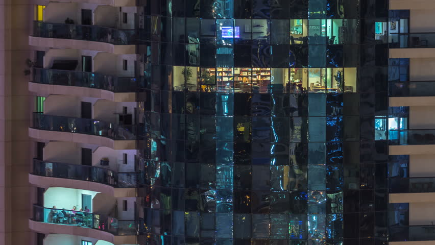 Windows of the multi-storey building of glass and steel lighting inside and moving people within timelapse. Aerial view of modern residential and office skyscrapers in Dubai marina. Pan down | Shutterstock HD Video #1011839942