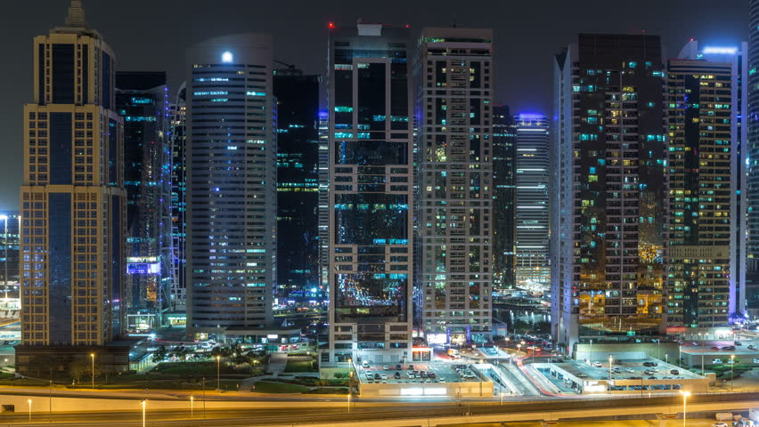 Aerial view of Jumeirah lakes towers with illuminated skyscrapers during all night timelapse with traffic on sheikh zayed road and metro line. Rooftop view from Dubai marina