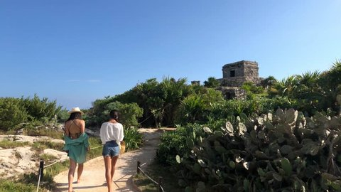 Two Girls Walking Up Path Along Coast of Tulum Mexico Tracking Shot