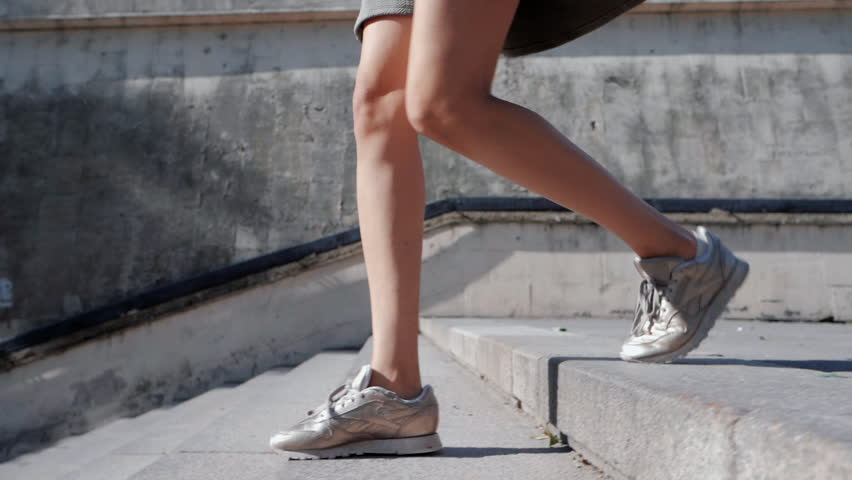 Close up of woman's legs in sneakers. GIrl goes down the city stairs. Slow motion.