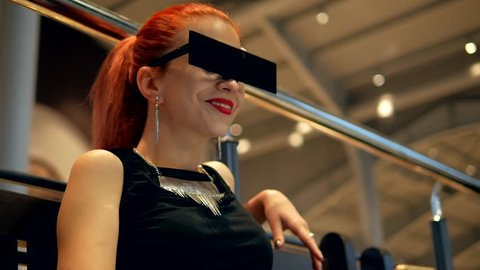 Stylish fashion red hair woman in black dress and square glasses watches mobile phone news