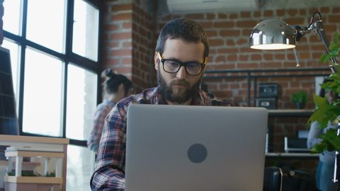 Sad bearded man watching laptop and telling bad news and sharing failures with diverse coworkers in office