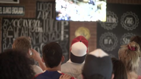 Football fans excitedly watching televised match at sports bar