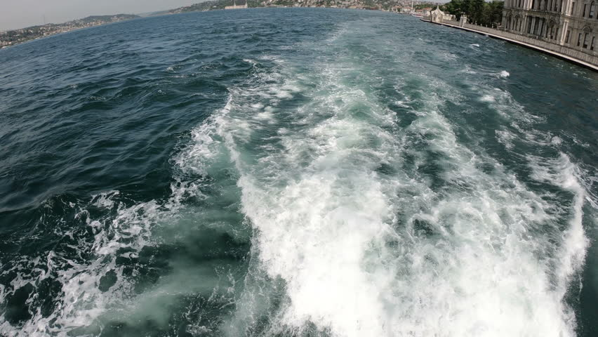 Point of View Shot from Ferry in Bosphorus Channel. White Foam Track Behind the SHip and Bosphorus Bridge in Frame.