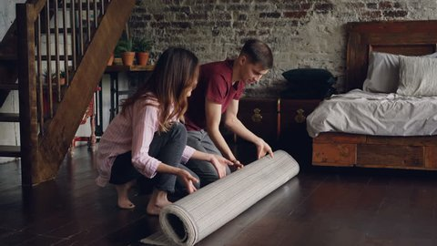 Young married couple is rolling out beautiful new carpet in bedroom at home then enjoying it. House interior, married life and happy people concept.