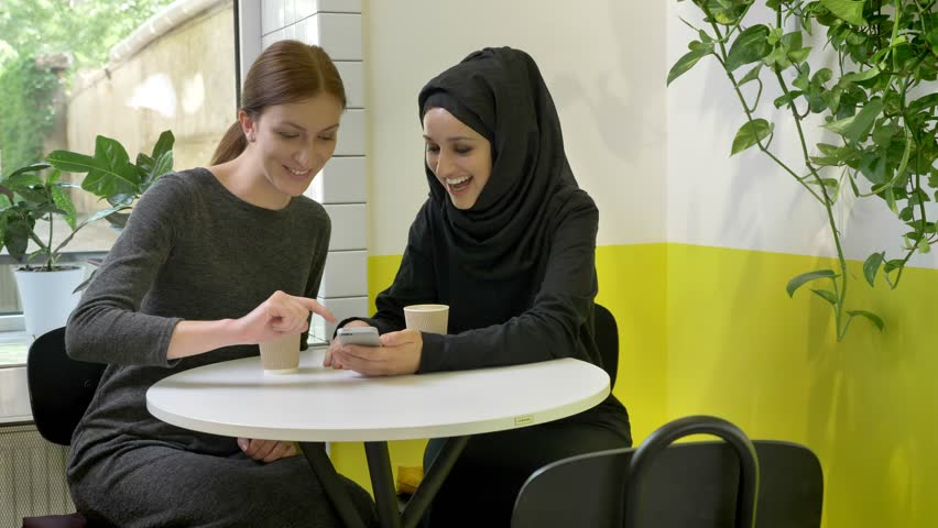 Two young beautiful womans sitting in cafe, one of them muslim woman in hijab, looking at phone, smiling and laughing