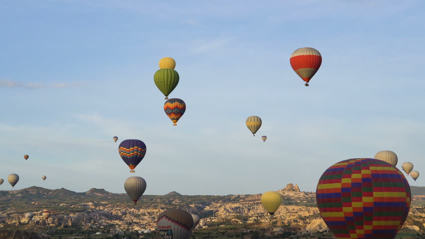 Lots of hot air balloons flying over valleys in Goreme, Turkey. Tourists from all over the world come to Cappadocia to make a trip in a hot-air balloons.