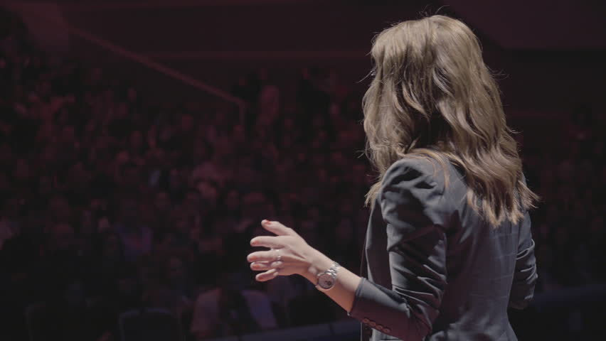 The female financial coach emotional gesturing talks from the stage with spectators at forum. Too many anonymous persons workers and students seat in large auditorium and watch workshop background | Shutterstock HD Video #1011955952