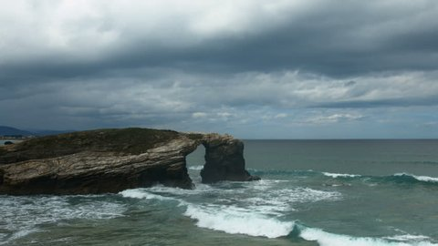 Long shot of stunning arched cliffs under dark clouds and strong waves at Costas do Catedrais in Galizia, Spain