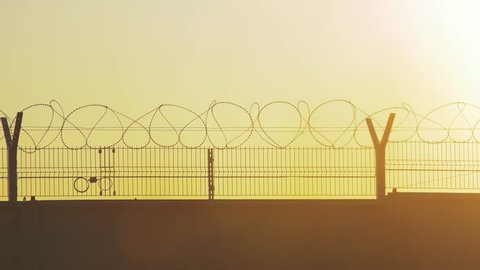 fence prison strict regime the silhouette barbed wire. illegal immigration fence from refugees. illegal lifestyle immigration concept prison prison fence