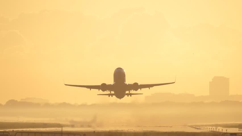 4K Passenger airplane take off during sunrise.