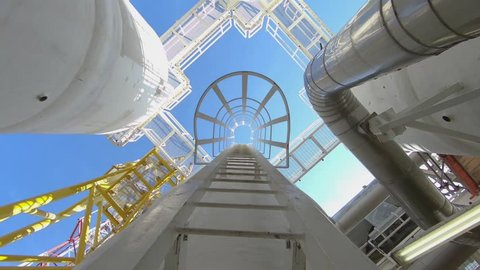 Offshore oil and gas engineer climb up to gases process vessel to inspect and observe quality of gas treatment process.
